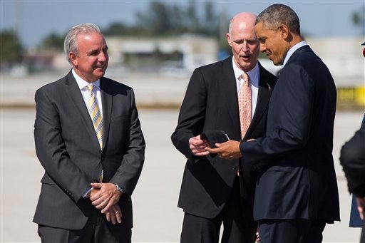 Miami-Dade County Mayor Carlos Gimenez watches at left as Florida Gov. Rick Scott, R-Fla. gives a Miami Marlins baseball cap to President Barack Obama upon the president's arrived at Miami International airport in Miami, Wednesday, Feb. 25, 2015. (AP)