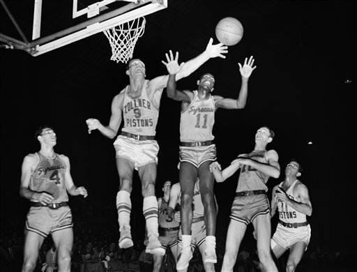 In this April 1955 file photo, Fort Wayne's Mel Hutchins (9) and Syracuse's Earl Lloyd (11) reach for the ball during an NBA basketball game in Indianapolis.