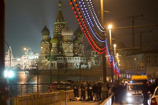Russian police investigate the the body of Boris Nemtsov, a former Russian deputy prime minister and opposition leader at Red Square with St. Basil Cathidral in the background in Moscow, Russia, Saturday, Feb. 28, 2015. Russia's Interior Ministry says Bor
