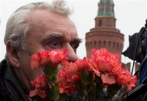 A man reacts as he lays flowers at the place where Boris Nemtsov, a charismatic Russian opposition leader and sharp critic of President Vladimir Putin, was gunned down, at Red Square in Moscow, Russia, Saturday, Feb. 28, 2015. Nemtsov was gunned down Satu