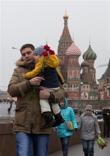 A Russian family walk to lay flowers at the place where Boris Nemtsov, a charismatic Russian opposition leader and sharp critic of President Vladimir Putin, was gunned down, at Red Square in Moscow, Russia, Saturday, Feb. 28, 2015. Nemtsov was gunned down