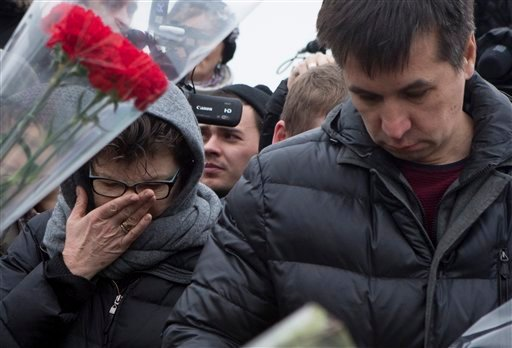 People react as they lay flowers at the place where Boris Nemtsov, a charismatic Russian opposition leader and sharp critic of President Vladimir Putin, was gunned down, at Red Square in Moscow, Saturday, Feb. 28, 2015. Nemtsov was gunned down Saturday ne