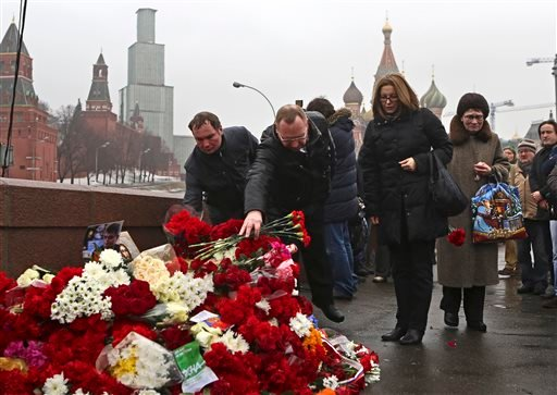 People lays flowers at the place where Boris Nemtsov, a charismatic Russian opposition leader and sharp critic of President Vladimir Putin, was attacked, at Red Square in Moscow, Russia, Saturday, Feb. 28, 2015. Nemtsov was gunned down Saturday near the K
