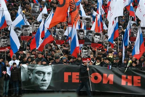 People carry a huge banner reading 'those bullets for everyone of us, heroes never die!' as they march in memory of opposition leader Boris Nemtsov who was gunned down on Friday, Feb. 27, 2015 near the Kremlin, in Moscow, Russia, Sunday, March 1, 2015. Th