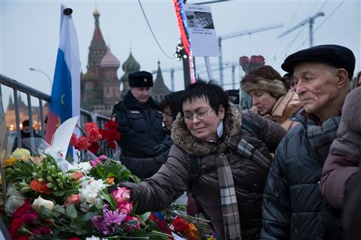 People lay flowers during a march next to the place where Boris Nemtsov, a charismatic Russian opposition leader and sharp critic of President Vladimir Putin, was gunned down on Friday, Feb. 27, 2015 near the Kremlin, with St, Basil Cathedral is in the ba