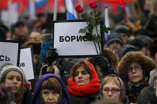 People march with posters reading ' fight!' near the place where Boris Nemtsov, a charismatic Russian opposition leader and sharp critic of President Vladimir Putin, was gunned down on Friday, Feb. 27, 2015 near the Kremlin, in Moscow, Russia, Sunday, Mar