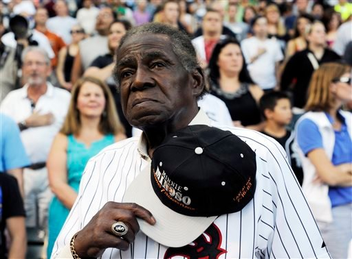 In a Aug. 24, 2013 file photo, former Negro Leaguer and Chicago White Sox player Minnie Minoso stands during the national anthem before a baseball game between the Chicago White Sox and the Texas Rangers, in Chicago. Major league baseball's first black pl
