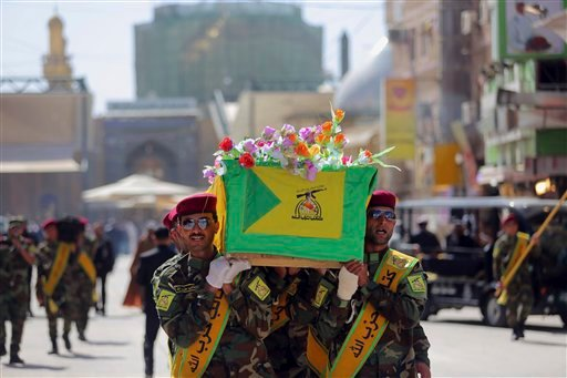 Iraqi Hezbollah fighters carry the coffin of their comrade, Ali Mansour, who his family says was killed in Tikrit fighting Islamic militants, during his funeral procession, in the Shiite holy city of Najaf, 100 miles (160 kilometers) south of Baghdad, Ira