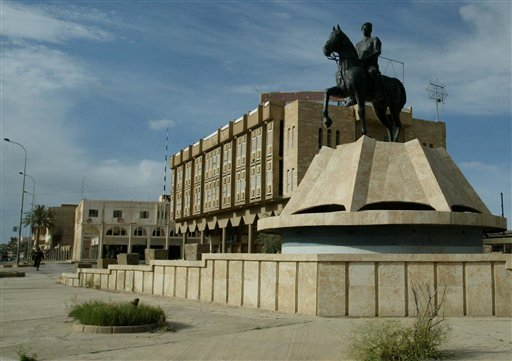In this Sunday, April 13, 2003 file photo, a statue of Iraqi President Saddam Hussein is seen as the streets are nearly deserted in central Tikrit, Iraq. Backed by allied Shiite and Sunni fighters, Iraqi security forces on Monday began a large-scale milit