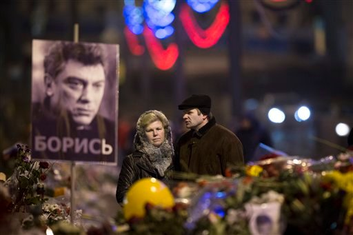 A couple comes to pay respects at the place where Boris Nemtsov, a charismatic Russian opposition leader and sharp critic of President Vladimir Putin, was gunned down on Friday, Feb. 27, 2015 near the Kremlin, in Moscow, Russia, Monday, March 2, 2015.
