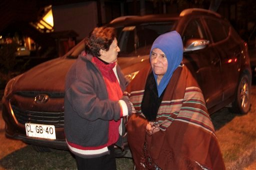 People leave their houses after Villarica volcano erupted near Pucon, Chile, early Tuesday, March 3 , 2015. The Villarica volcano erupted Tuesday around 3 a.m. local time (0600 GMT), according to the National Emergency Office, which issued a red alert and