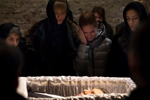 Dina Eidman, mother of Boris Nemtsov, left, and other relatives pay their last respects near the coffin of Nemtsov, a charismatic Russian opposition leader and sharp critic of President Vladimir Putin, during a farewell ceremony inside the Sakhavov's cent