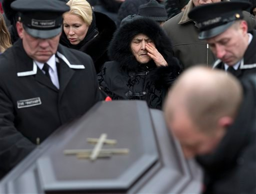 Boris Nemtsov's mother Dina Eidman, center, relatives and friends stand at the coffin during a burial ceremony at Troekurovskoye cemetery in Moscow, Russia, Tuesday, March 3, 2015. One by one, thousands of mourners and dignitaries filed past the white-lin
