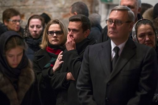 Opposition leaders, former Russian Prime Minister Mikhail Kasyanov, right, and Ilya Yashin, center, together with other relatives and friends pay their last respects by the coffin of Boris Nemtsov, a charismatic Russian opposition leader and sharp critic