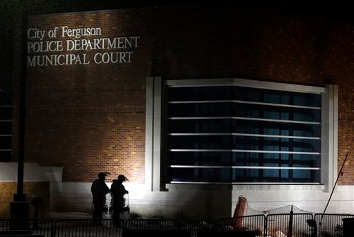 In this Nov. 26, 2014, file photo, nembers of Missouri National Guard stand outside of the Ferguson Police Department and the Municipal Court in Ferguson, Mo. (AP Photo/Jeff Roberson, File)