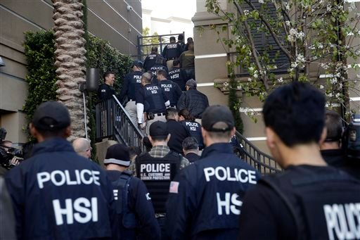 Federal agents enter an upscale apartment complex March 3, 2015, in Irvine, Calif. Federal agents swarmed the complex where authorities say a birth tourism business charged pregnant women $50,000 for lodging, food and transportation.(AP Photo/Jae C. Hong)