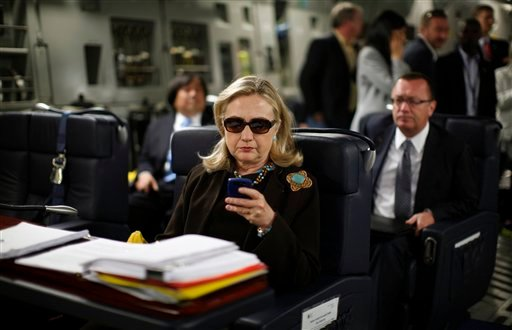 In this Oct. 18, 2011, file photo, then-Secretary of State Hillary Rodham Clinton checks her Blackberry from a desk inside a C-17 military plane upon her departure from Malta bound for Tripoli, Libya. (AP Photo/Kevin Lamarque, Pool, File)