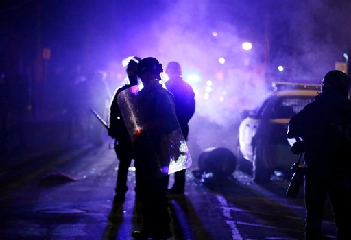In this Nov. 25, 2014 file photo, police officers watch protesters as smoke fills the streets in Ferguson, Mo. after a grand jury's decision in the fatal shooting of Michael Brown.(AP Photo/Charlie Riedel, File)