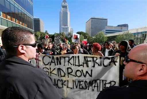 Protestors carry a banner during a rally in front of the police administration building in downtown Los Angeles on Tuesday, March 3, 2015. (AP)