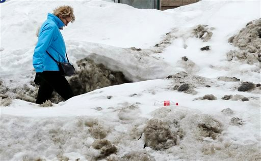 A woman navigates high snow banks as she walks through the Chinatown neighborhood of Boston, Wednesday, March 4, 2015. (AP Photo/Charles Krupa)