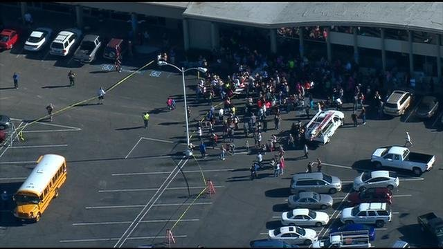 Students from Lindo Park School wait in a parking lot during Thursday's lockdown.