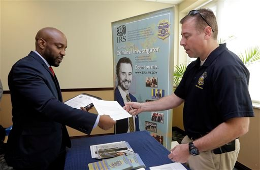 In this Feb. 6, 2015 photo, U.S. Marine Corps Veteran Arlington Robertson, of Fort Lauderdale, left, hands his resume to an Internal Revenue Service Special Agent, at the annual Veterans Career and Resource Fair in Miami. The Labor Department releases emp