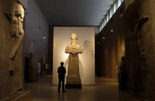 """In this Nov. 24, 2009 file photo, a journalist looks at an Assyrian statue, center, in front of two Assyrian human-headed winged bulls at Iraq's national museum, in Baghdad. Islamic State militants """"bulldozed"""" the renowned archaeological site of the ancie"""