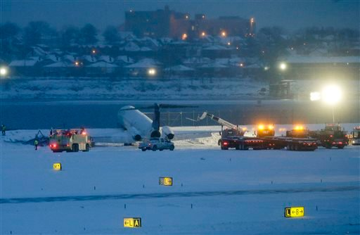 A Delta plane rests on a berm near the waters of Flushing Bay at LaGuardia Airport in New York on Thursday, March 5, 2015. The plane, from Atlanta, skidded off the runway during landing, and crashed through a chain-link fence. (AP Photo/Frank Franklin II)