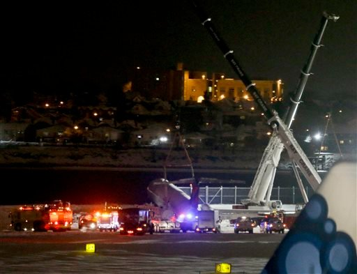 Crews work near a Delta plane that rests on a berm near the water at LaGuardia Airport, Thursday, March 5, 2015, in New York. The plane, from Atlanta, skidded off the runway while landing, and crashed through a chain-link fence. (AP Photo/Frank Franklin I