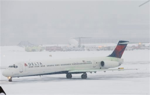 A Delta plane passes Delta Flight 1086 that rests on a berm near the water at LaGuardia Airport, Thursday, March 5, 2015, in New York. The plane, from Atlanta, skidded off the runway while landing, and crashed through a chain-link fence. (AP Photo/Frank F