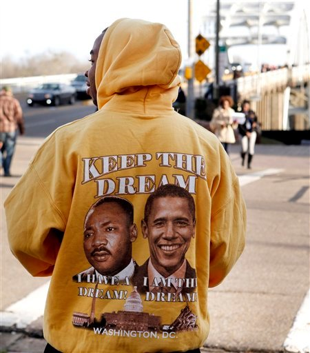 "A man passes out programs wearing a ""Keep The Dream,"" jacket as setup begins for the 50th Anniversary March over the Edmund Pettus Bridge, Friday, March. 6, 2015, in Selma, Ala. This weekend marks the 50th anniversary of ""Bloody Sunday,"" a civil rights ma"