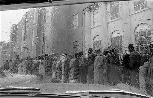 In this Feb. 17, 1965 file photo, African Americans stand in line in the rain to try to register for a voter registration test in Selma, Ala. (AP Photo/File)