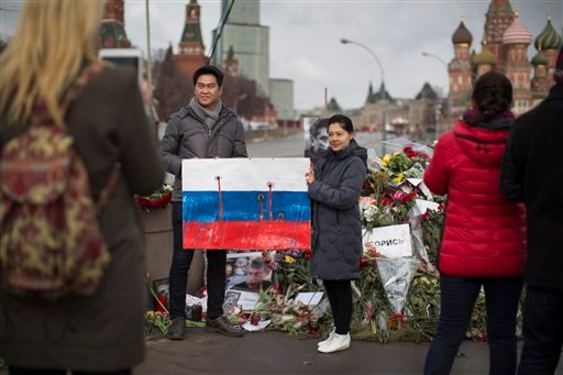Tourists hold a poster symbolically showing a Russian flag riddled with bullet holes as they pose for a photo at the place where Boris Nemtsov, a charismatic Russian opposition leader and sharp critic of President Vladimir Putin, was gunned down on Friday