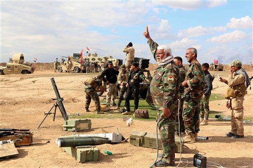 In this Wednesday, March 4, 2015 photo, Iraqi army soldiers and volunteers prepare to launch mortar shells and rockets against Islamic State militant positions outside Tikrit, 80 miles (130 kilometers) north of Baghdad, Iraq. Iranian-backed Shiite militia