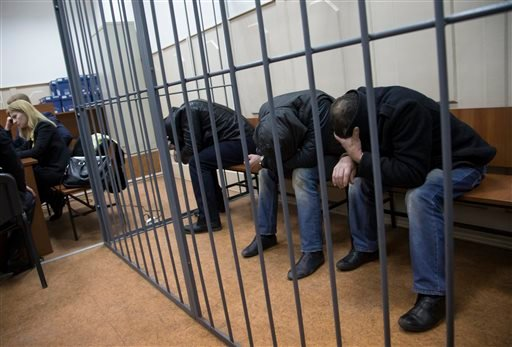Three men, from the left: Tamerlan Eskerkhanov, Shagid Gubashev and Khamzad Bakhaev suspected of involvement in the killing of Boris Nemtsov sit in a court room in Moscow, Russia, Sunday, March 8, 2015. A Russian court on Sunday charged two men in the kil