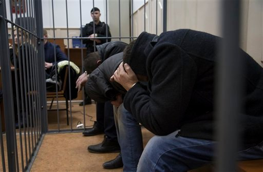 Three men, from right: Khamzad Bakhaev, Shagid Gubashev and Tamerlan Eskerkhanov, suspected of involvement in the killing of Boris Nemtsov sit in a court room in Moscow, Russia, Sunday, March 8, 2015. A Russian court on Sunday charged two men in the killi