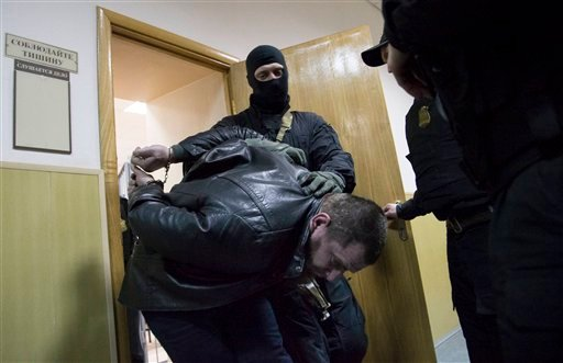 Police escort Tamerlan Eskerkhanov one of five suspects in the killing of Boris Nemtsov from a court room in Moscow, Russia, Sunday, March 8, 2015. A Russian court on Sunday charged two men in the killing of leading opposition figure Boris Nemtsov and ord