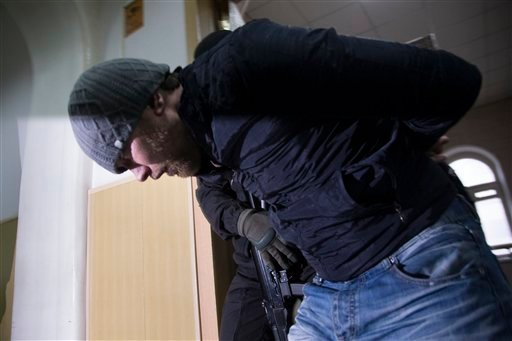 Police escort Anzor Gubashev, one of five suspects in the killing of Boris Nemtsov from a court room in Moscow, Russia, Sunday, March 8, 2015. A Russian court on Sunday charged two men in the killing of leading opposition figure Boris Nemtsov and ordered