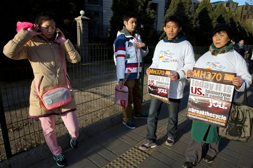 Relatives of passengers on board the missing Malaysia Airlines Flight 370 protest near the Malaysian Embassy in Beijing on the one year anniversary, Sunday, March 8, 2015. Vowing never to give up on the desperate search for the plane, family members of th