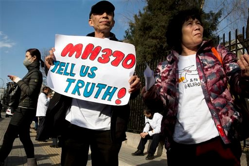 Relatives of passengers on board the missing Malaysia Airlines Flight 370 protest near the Malaysian Embassy in Beijing on the one year anniversary, Sunday, March 8, 2015. Families of the 239 people on board the plane on Sunday marked the anniversary of t