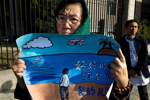 "A woman whose son was on board the missing Malaysia Airlines Flight 370 protests with a banner which reads ""Mother's heart is broken, where are you my son"" near the Malaysian Embassy in Beijing on the one year anniversary, Sunday, March 8, 2015. Families"