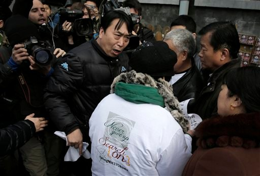 A policeman grabs papers from the relatives of passengers on board the Malaysia Airlines Flight 370 that went missing on March 8, 2014, after they showed the papers to journalists near Yonghegong Lama Temple in Beijing Sunday, March 8, 2015. Families of t