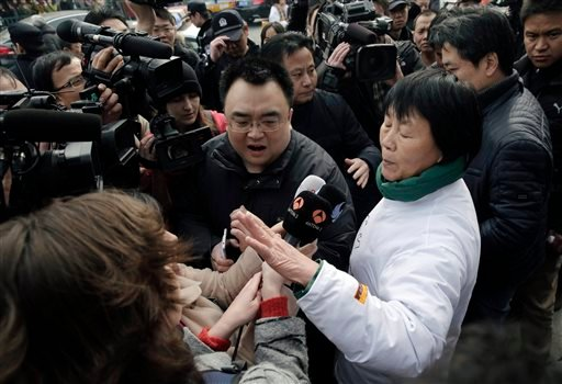 Dai Shuqin, front right, and Jiang Hui, rear right, relatives of passengers on board the Malaysia Airlines Flight 370 that went missing on March 8, 2014, is intervened by policemen as they try to speak to journalists near Yonghegong Lama Temple during a g