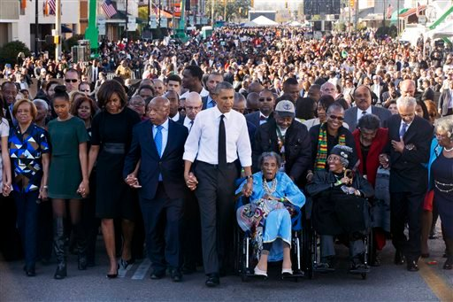 "President Barack Obama, center, walks as he holds hands with Amelia Boynton Robinson, who was beaten during ""Bloody Sunday,"" as they and the first family and others including Rep. John Lewis, D-Ga,, left of Obama, walk across the Edmund Pettus Bridge in S"