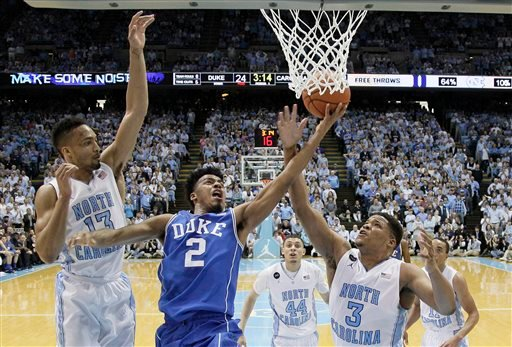 North Carolina's J.P. Tokoto (13) and Kennedy Meeks (3) defend as Duke's Quinn Cook (2) drives to the basket during the first half of an NCAA college basketball game Saturday, March 7, 2015, in Chapel Hill, N.C. Duke won 84-77. (AP Photo/Gerry Broome)