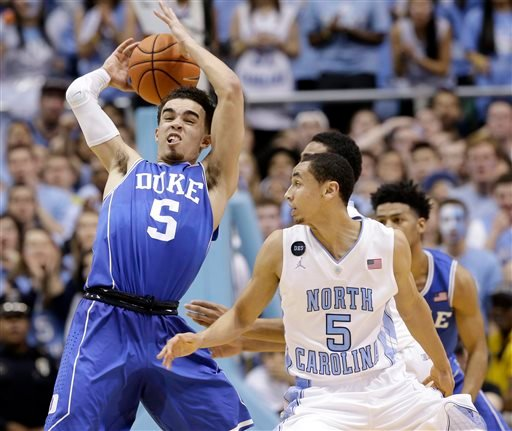North Carolina's Marcus Paige (5), right, defends as Duke's Tyus Jones (5) grabs the ball during the second half of an NCAA college basketball game Saturday, March 7, 2015, in Chapel Hill, N.C. Duke won 84-77. (AP Photo/Gerry Broome)