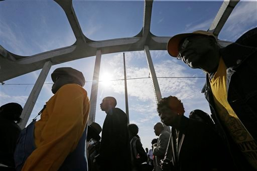"""Crowds of people walk toward Selma after taking a symbolic walk across the Edmund Pettus Bridge, Sunday, March 8, 2015, in Selma, Ala. This weekend marks the 50th anniversary of """"Bloody Sunday,"""" a civil rights march in which protestors were beaten, trampl"""