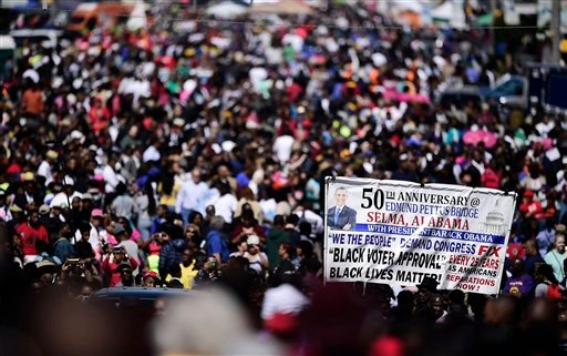 """Crowds gather near the Edmund Pettus Bridge, Sunday, March 8, 2015, in Selma, Ala. This weekend marks the 50th anniversary of """"Bloody Sunday,' a civil rights march in which protestors were beaten, trampled and tear-gassed by police at the Edmund Pettus Br"""