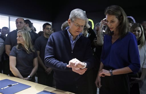 Apple CEO Tim Cook, left, and Christy Turlington Burns, founder of Every Mother Counts, look at the new Apple Watch in the demo room after an Apple event on Monday, March 9, 2015, in San Francisco.