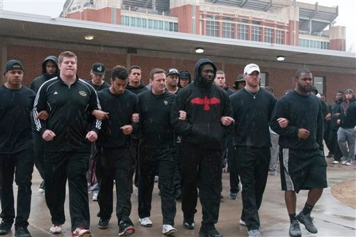The University of Oklahoma football team and coaches line up wearing all black in the Everest Training Center in protest of the Sigma Alpha Epsilon fraternity at the University of Oklahoma on Monday, March. 9, 2015. The Sigma Alpha Epsilon fraternity has